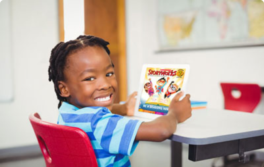 Second grader smiling with Storyworks 2 magazine at desk